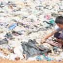 Dreng sorterer affald på losseplads
